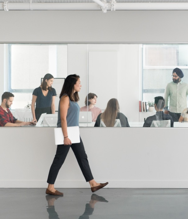 Woman walking down a hallway, passing by windows into a conference room